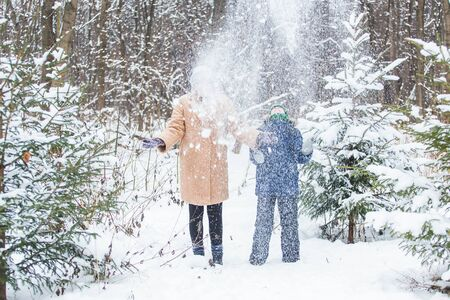 Parenting, fun and season concept - Happy mother and son having fun and playing with snow in winter forest.