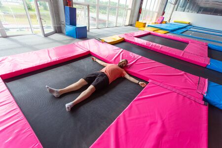 Fitness, fun, leisure and sport activity concept - Man lying on a trampoline indoors, top view
