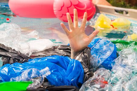 Plastic pollution and environmental problem, mans hand in plastic sea