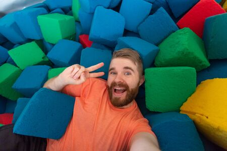 Fitness, fun, leisure and sport activity concept - Funny man taking selfie on a trampoline indoors