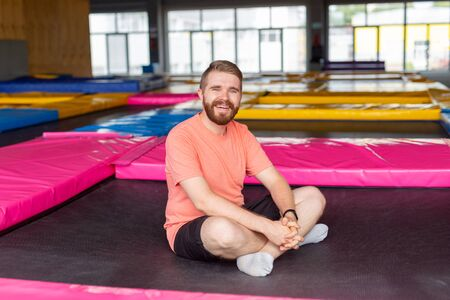 Fitness, fun, leisure and sport activity concept - Man sitting on a trampoline indoors