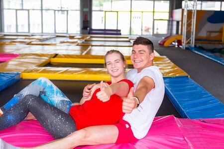 Fitness, fun, leisure and sport activity concept - Man and woman sits together on a trampoline indoors Banco de Imagens