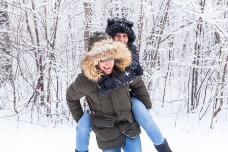 Portrait of happy young couple in winter park with their friend behind