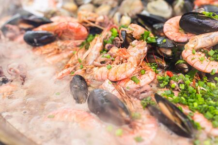 Street food and meal - Spanish paella close-up with shrimp and clams.
