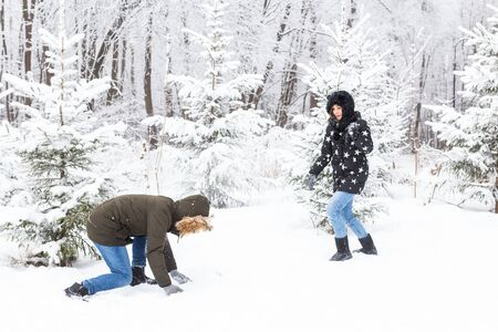 Lifestyle, season and leisure concept - Funny couple playing snowball in winter park. Stock Photo