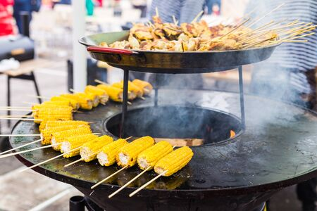 Preparing hot grilled corn outdoors at summer. Asian street food
