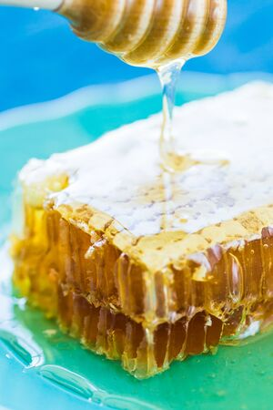 Honey with wooden honey dipper and honeycombs, close-up