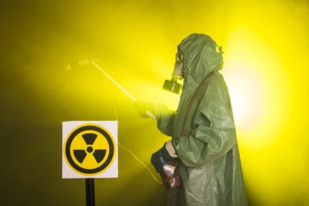Radiation and danger concept - Man in the gas mask and chemical suit. The worker doing measure radioactivity