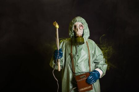 Radiation and danger concept - Man in old protective hazmat suit. Stock Photo
