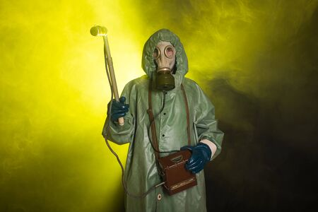 Man in protective clothing and a gas mask on a dark background