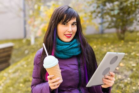 Technologies, urban and people concept - Student young woman reading an ebook or tablet in an urban autumn park