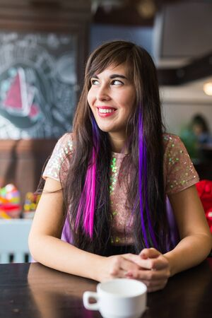 Young stylish trendy woman with multi-coloured strand in hair sits in cafe