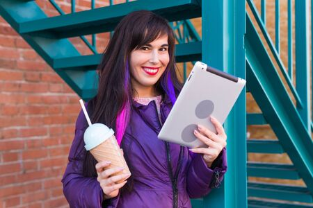 Technologies, urban and people concept - Woman reading an ebook or tablet in an urban backgrounds