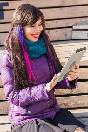 Technologies, urban and people concept - Student young woman reading an ebook or tablet in a city