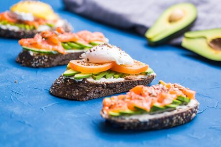 Sandwiches with smoked salmon, eggs, sauce and avocado on blue background. Concept of breakfast and healthy nutrition