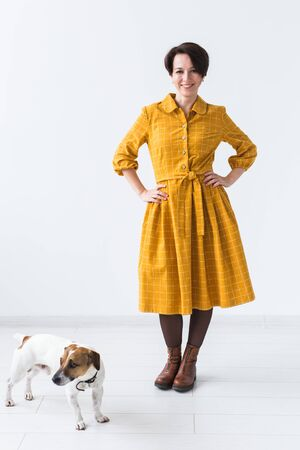 Cheerful young woman posing in a yellow dress with her beloved dog Jack Russell Terrier standing on a white background. The concept of casual wear.