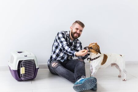 Dog carrying bags and pets owner concept - Attractive cheerful male in plaid shirt holds favourite pet. Happy bearded man with his jack russell terrier