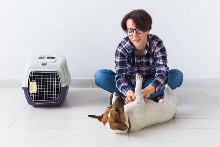 Dog carrying bags and pets owner concept - Attractive cheerful female in plaid shirt holds favourite pet. Happy woman with her jack russell terrier