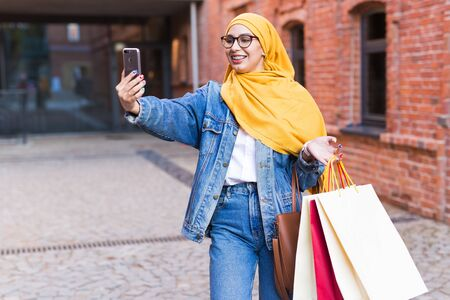 Sale, technologies and buying concept - Happy arab muslim woman taking selfie outdoors after shopping