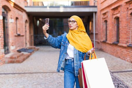 Sale, technologies and buying concept - Happy arab muslim woman taking selfie outdoors after shopping Stockfoto