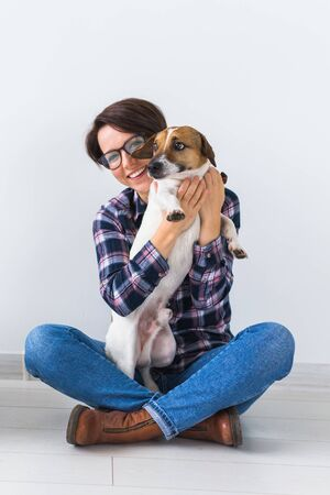 Pets owner concept - Attractive cheerful female in plaid shirt holds favourite pet. Happy woman with her jack russell terrier