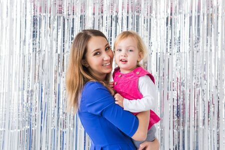 Childhood, love and family concept - Mother holds baby daughter on shiny background. Close-up