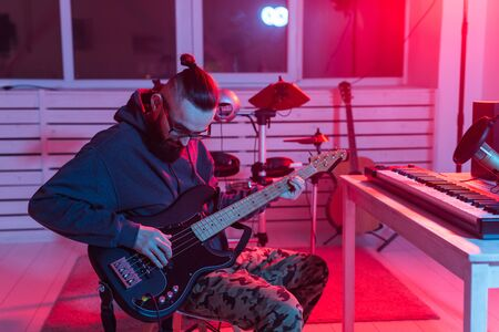 Create music and a recording studio concept - Bearded man guitarist recording electric guitar track in home studio.