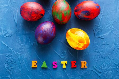 Multi-colored wooden letters making up the words happy easter and decorative colourful eggs on a blue background.