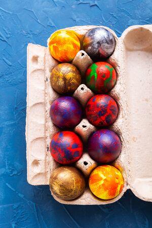 Handmade painted Easter eggs in egg box.