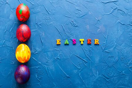 Multi-colored wooden letters making up the words happy easter and decorative colourful eggs on a blue background. Top view.