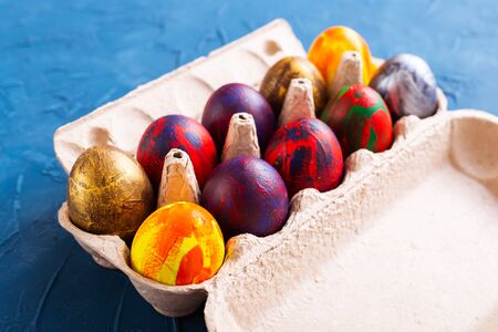 Handmade painted Easter eggs in egg box, close-up