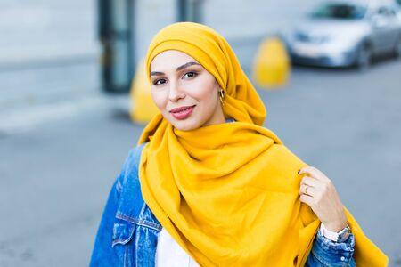 Beautiful Arabic muslim woman wearing yellow hijab, stylish female face portrait over city street.
