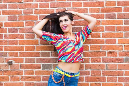 Fashion and urban style concept - Portrait of a beautiful woman in blue jeans against a white brick wall.