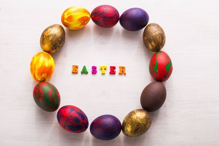 Multi-colored wooden letters making up the words happy easter and decorative colourful eggs on a white background with copy space.