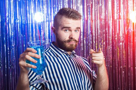 Alcoholism, fun and fool concept - Drunk guy at party in a nightclub.