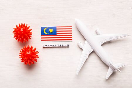 Flight ban and closed borders for tourists and travelers with coronavirus covid-19. Airplane and flag of Malaysia on a white background. Coronavirus pandemic. Stock Photo