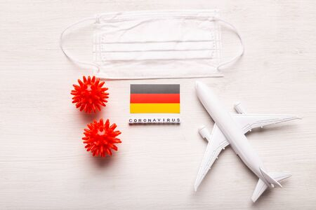 Plane model and face mask and flag Germany. Coronavirus pandemic. Flight ban and closed borders for tourists and travelers with coronavirus covid-19 from Europe and Asia. Stock Photo