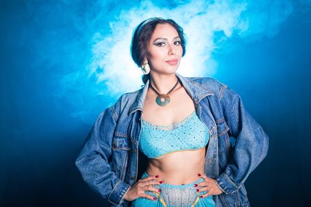 Magic, cosplay and fairy tale concept - Portrait of a young woman in the image of an Eastern fairy Princess on blue background. Standard-Bild
