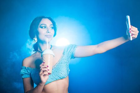 Magic, cosplay and fairy tale concept - Portrait of a young woman in the image of an Eastern fairy Princess takes selfie on blue background.