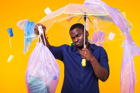 Problem of trash, plastic recycling, pollution and environmental concept - confused man carrying garbage bag on yellow background