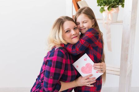Happy mothers day. Child daughter congratulates mom and gives her postcard. Mum and kid girl smiling and hugging. Family holiday and motherhood. Banco de Imagens