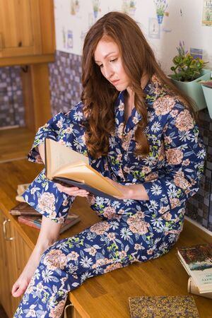 Young red-haired woman relaxing at home reading book. Quarantine, isolation, coronavirus pandemic world. Stay at home.
