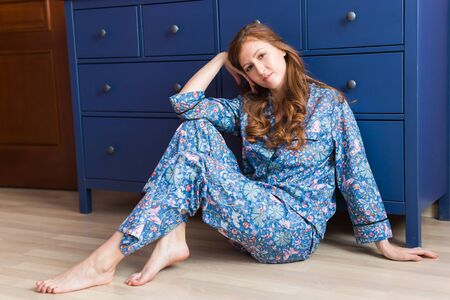 Girl sitting on the floor at home. Quarantine, isolation, coronavirus pandemic world. Stay at home.