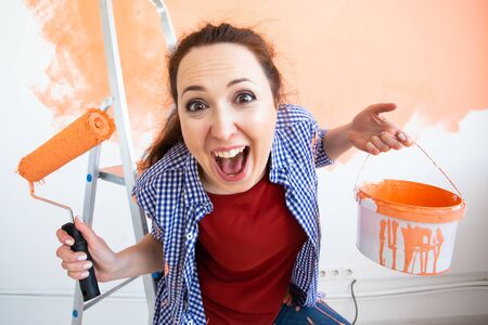 Renovation, redecoration and repair concept - Funny woman painting wall in new home.
