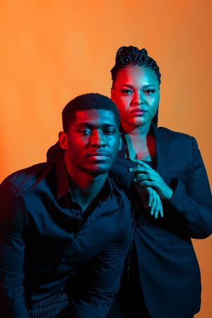Dark neon portrait of young african american man and woman. Red and blue light.