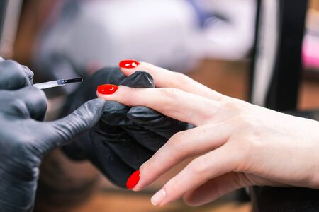 Master applied varnish drawing on nails gel in manicure salon, close-up. Gel polish concept