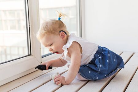 Hearing aid in baby girl's ear. Toddler child wearing a hearing aid at home. Disabled child, disability and deafness. Stock Photo