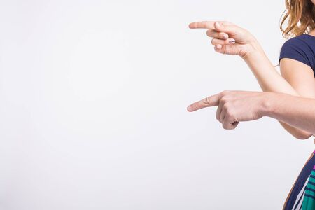 Couple pointing at the left corner with fingers standing isolated over white background. Copy space for product advertisement.