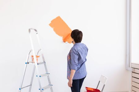 Pretty middle-aged woman with painting roller indoors. Redecoration, renovation, apartment repair and refreshment.