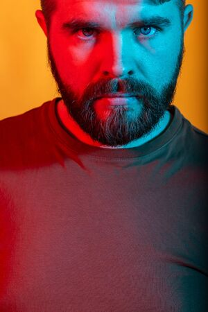 Neon light studio portrait of attractive male model with mustaches and beard wears t-shirt, close-up.